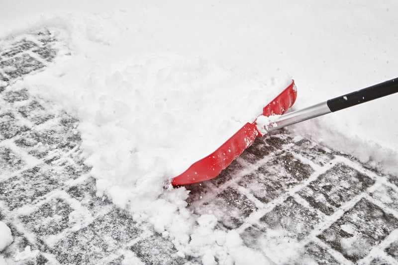 Man Shovelling Snow with Red Shovel