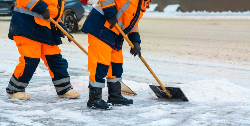 Communal Services Workers Sweep Snow from Road